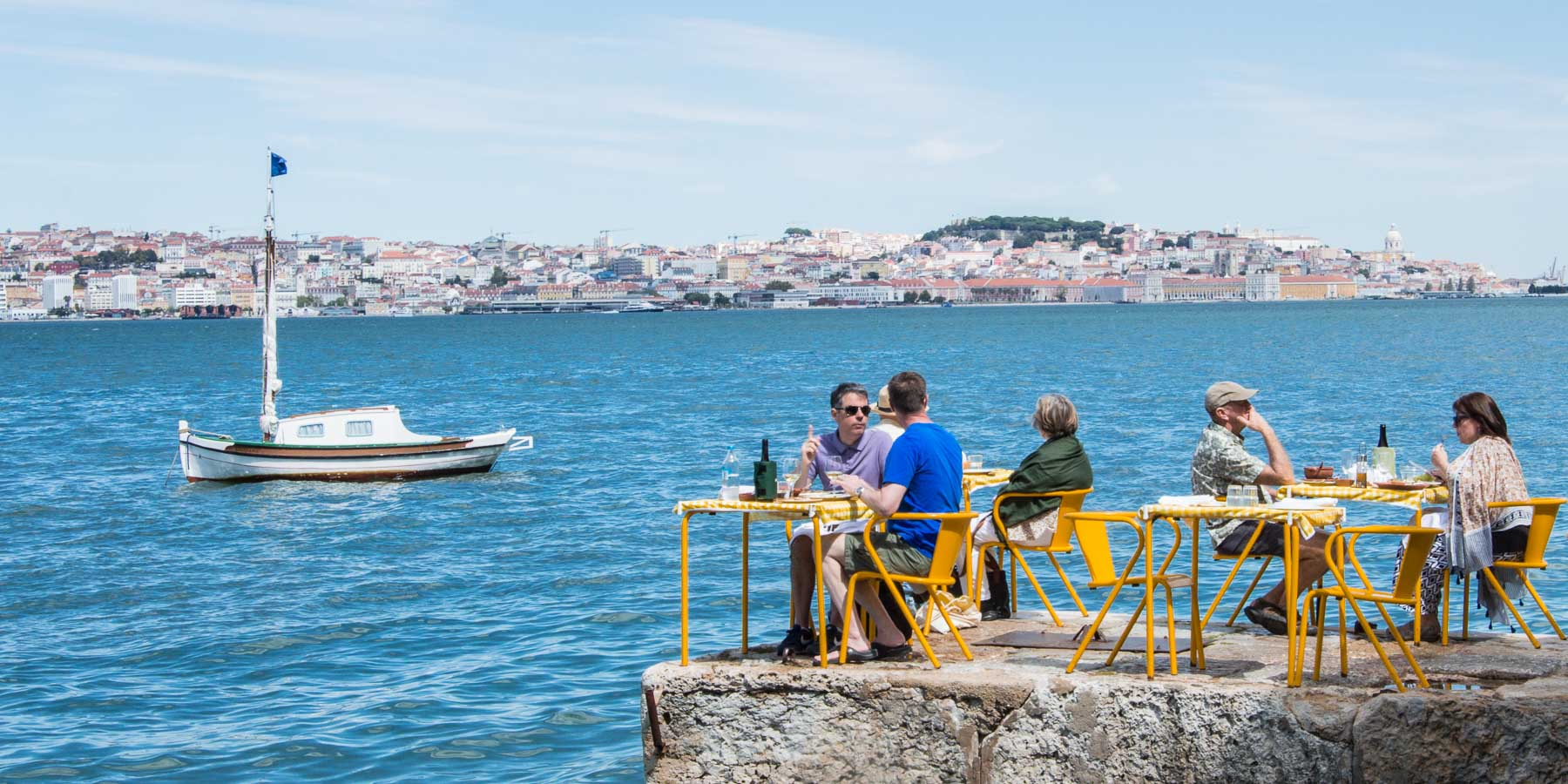 Three couples having lunch at the end of a dock on the Tagus River, Lisbon.