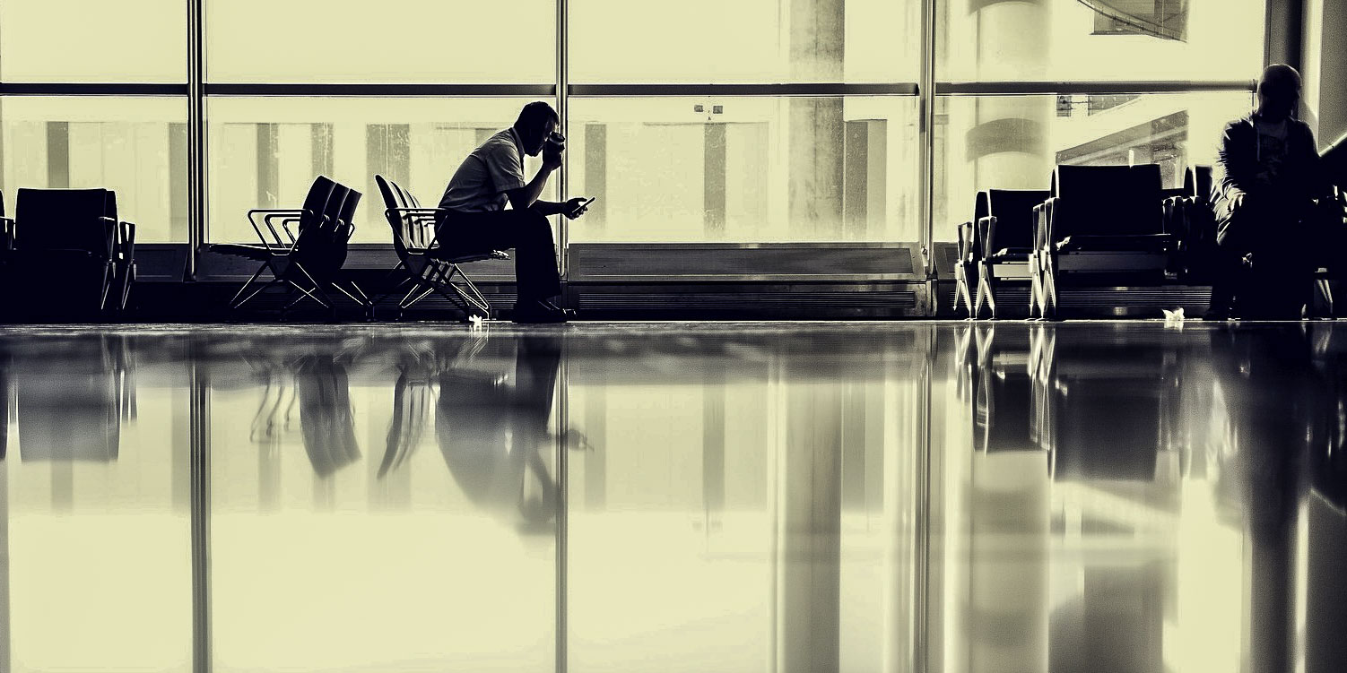 Man sitting in an airport terminal looking at his mobile.