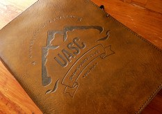 UASC Snowsports Club logo on brown leather journal - Earthworks Journals