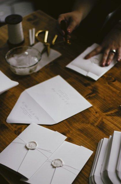 girl sealing wedding invitations with wax seals