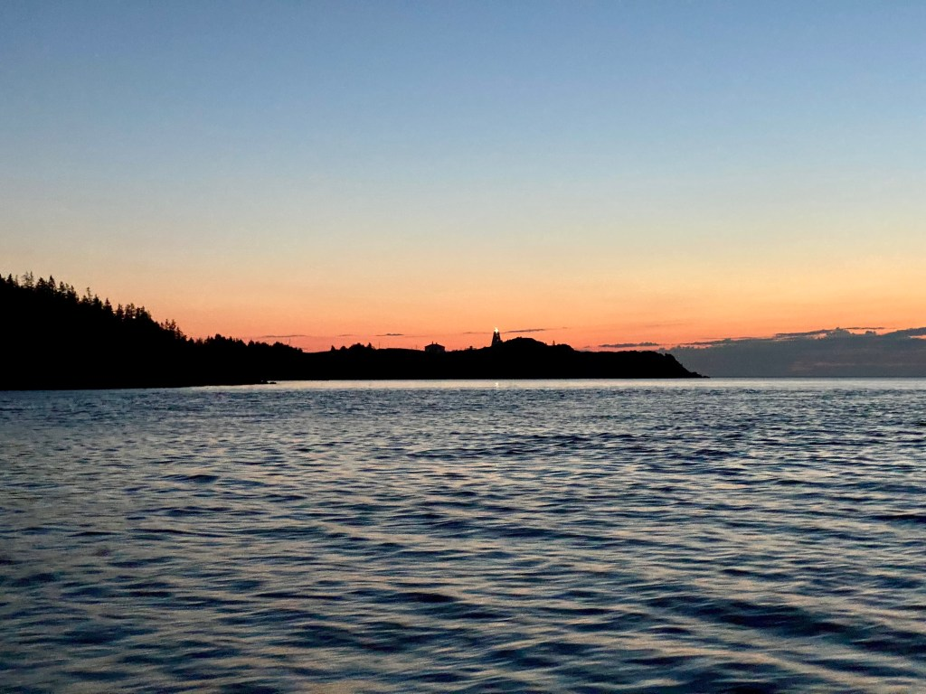 Swallow Tail Lighthouse in the early morning hours across calm waters with sunrise in the background