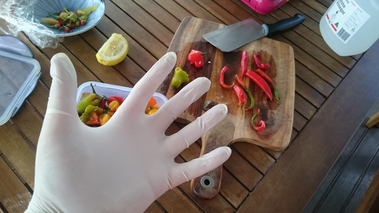 A latex-gloved hand over a board of chillies