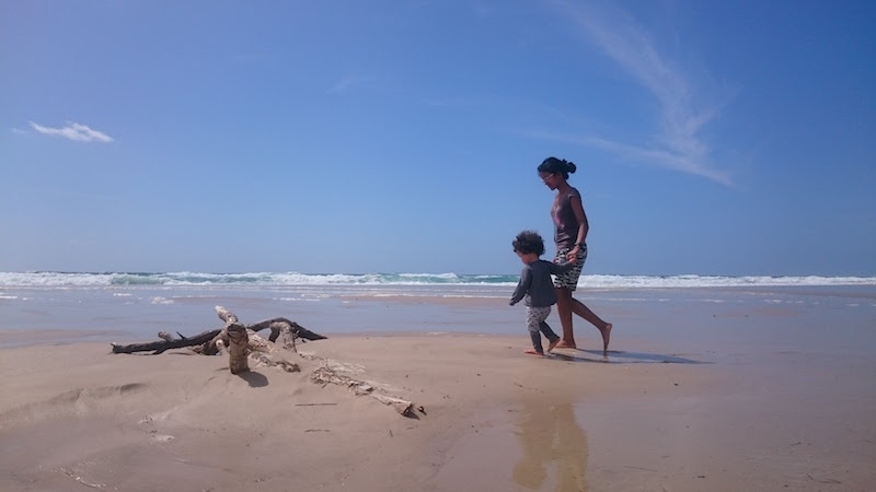 Toddler and mum walking on the beach
