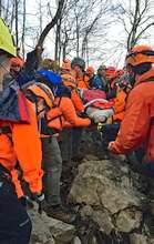 SAR team carrying subject over rough terrain.  COVID-19 Impacts on hiking extend to the rescuers as well as the hiker being rescued.