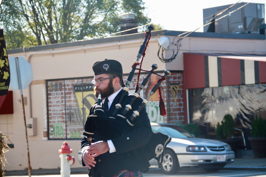 The Lone Piper, Aaron Lindo, leads the parade.