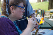 Over 15 people participated in the glass bead making village area, including Lady Carowyn Silveroak, pictured here.