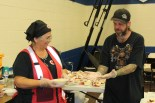 Red Cross volunteer Paulette Fernekees gets a hand serving supper from shelter resident Patrick Rabon