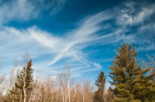 """High cirrus clouds create a broad """"X"""" in a blue sky on Sunday afternoon."""