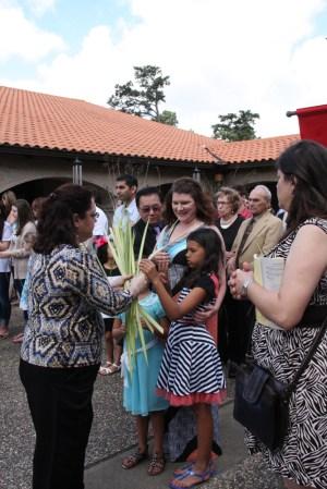 Valerie Brocato distributes palms to parishioners.