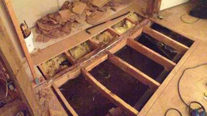an image looking down into a large hole in the floor of our homestead. it is being repaired