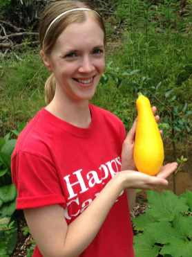 Jenn holds her first yellow squash harvested from our homestead