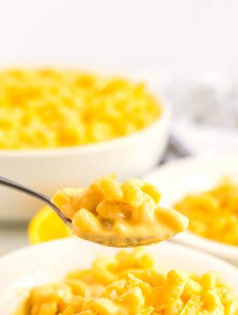 Cheesy and creamy mac and cheese on a serving spoon.