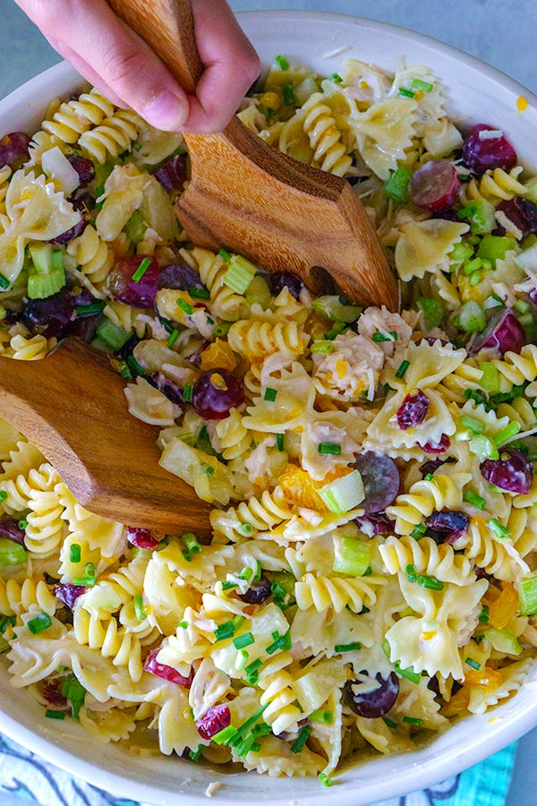 Pasta salad being picked up with salad servers.
