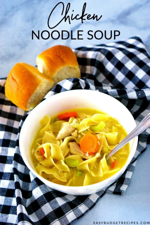 Chicken noodle soup in a white bowl with text overlay for Pinterest.