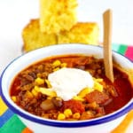 Ground beef chili garnished with shredded cheese and sour cream.