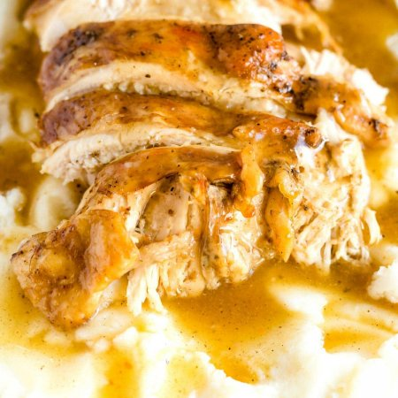 Close up image of slices of instant pot turkey breast on a bed of mashed potatoes and gravy.