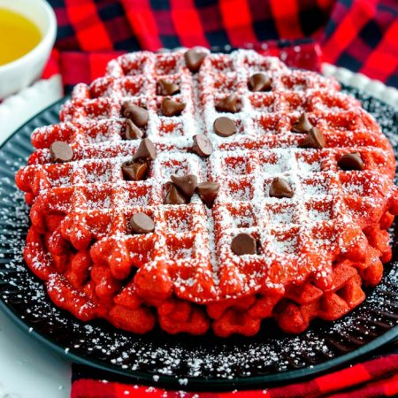 Waffles stacked on top of each other with powdered sugar sugar and chocolate chips.