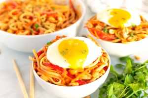 noodles topped with a fried egg with a runny yolk.