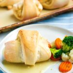 Chicken pillow on a white plate with steamed vegetables.