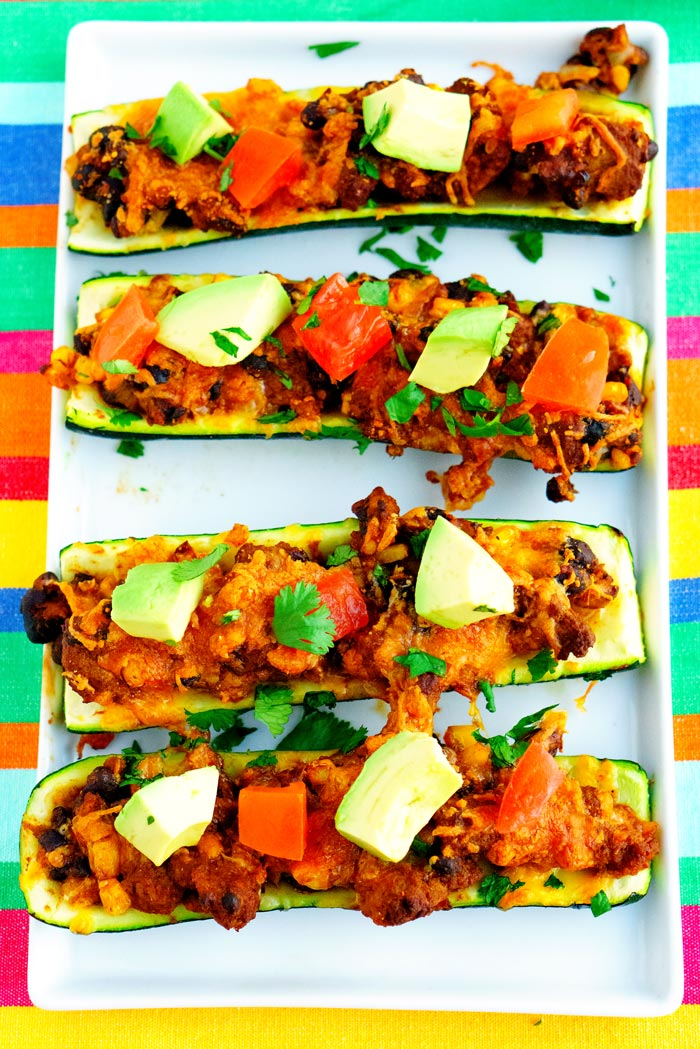 Overhead picture of zucchini taco boats on a white platter.