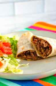 Machaca burrito cut in half on a white plate with shredded lettuce and chopped tomatoes.
