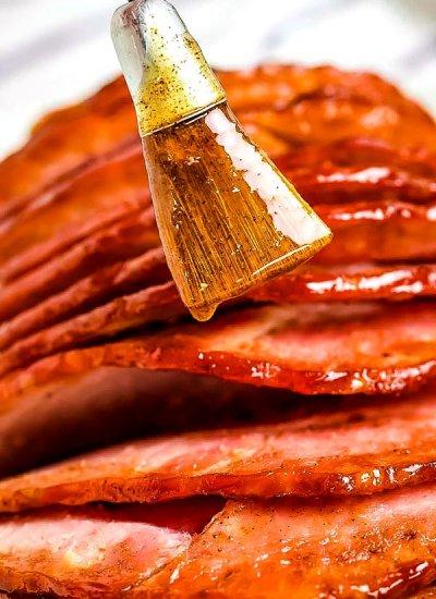 Brushing on the glaze of our copycat honey baked ham.