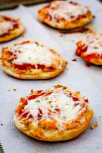 Close up of English muffins pizzas on a baking sheet.