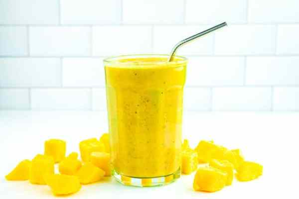 A mango smoothie surrounded by chunks of mango.