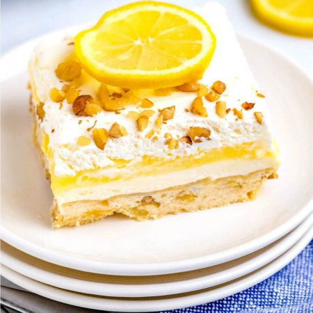 A slice on lemon lush on a white plate showing all of its 4 layers.