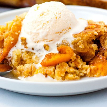 Close up of peach cobbler with a scoop of vanilla ice cream on a white plate.