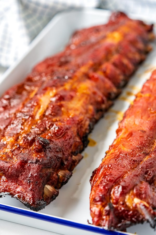 A close up picture of 2 racks of ribs that were cooked on the grill.