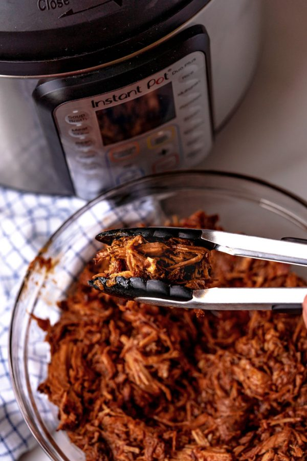 Tongs picking up a scoop of Instant Pot Pulled Pork.
