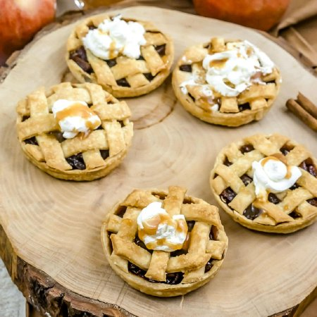 The mini pies on a wood serving plate.