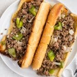 An overhead picture of two sloppy joes on a white plate.