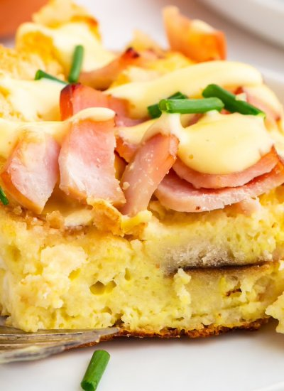A slice of overnight eggs benedict casserole on a white plate with hollandaise sauce drizzled over it.