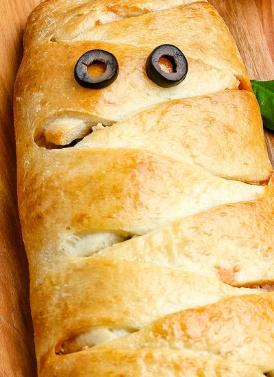 The mummy calzone on a wooden cutting board.