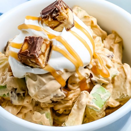 A close up of Snickers Salad with extra cool whip and caramel.