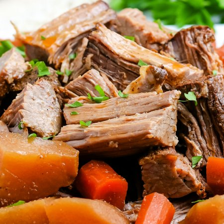 Shredded pot roast on a white platter with roasted potatoes and carrots.