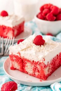 Slices of the finished Raspberry Jello Poke Cake on white plates.