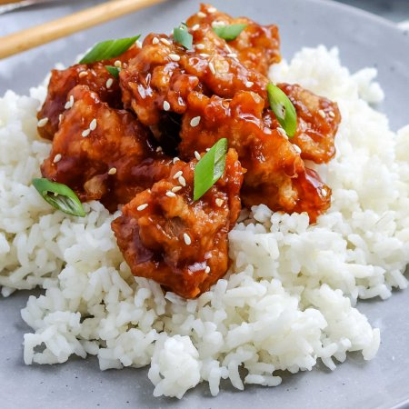 A close up picture of General Tso Chicken on top of rice.