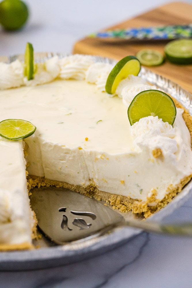 A slice taken out of a key lime pie.