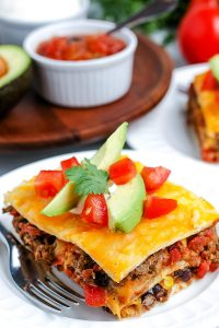 A close up pickets of a slice of Mexican Lasagna made with flour tortillas.
