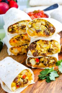 Three Breakfast Burritos cut in half and stacked on top of each other.