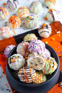 A bowl full of Cookie Dough Balls decorated for Halloween.