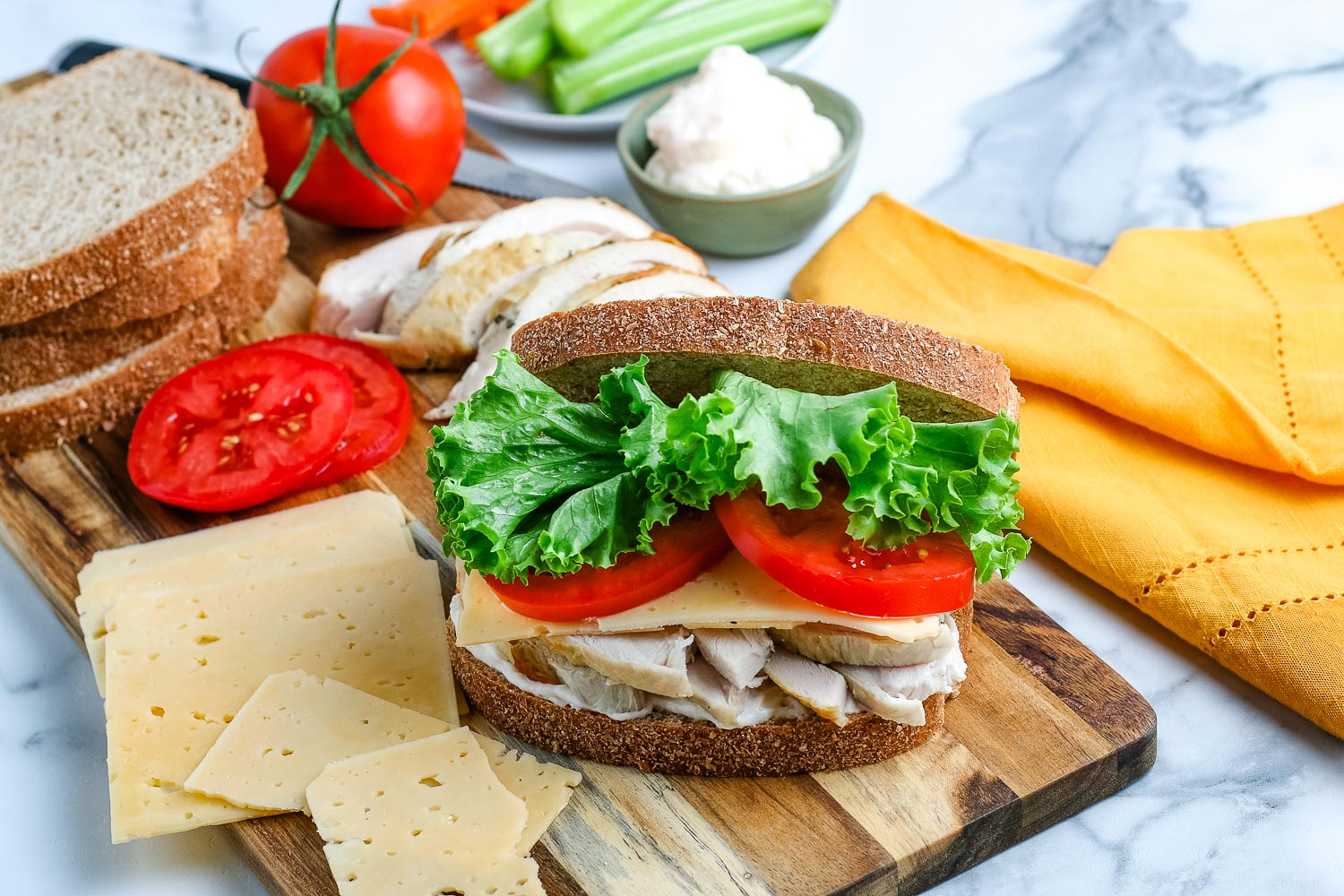 Leftover Turkey Sandwich on a wooden cutting board surrounded by other sandwich ingredients.