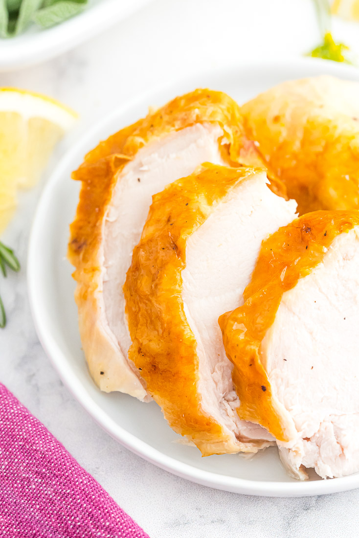 Thick slices of roast turkey on a white serving platter.