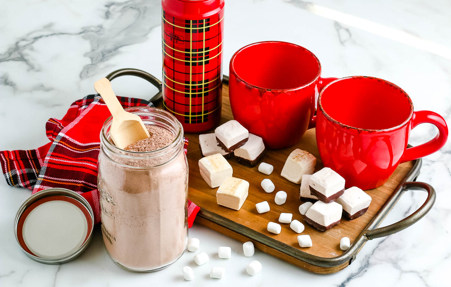Homemade Hot Chocolate Mix on a table top with mugs and marshmallows.