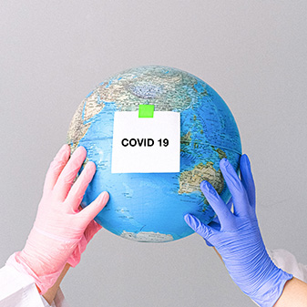 Globe with Covid-19 sign held by two gloved scientists