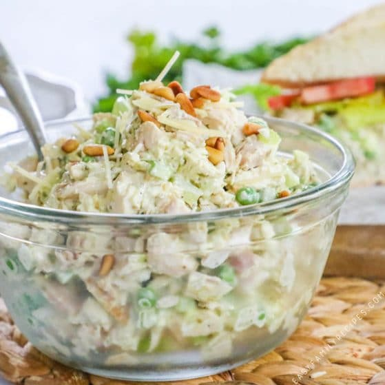 Pesto Chicken Salad prepared in a glass bowl with a spoon