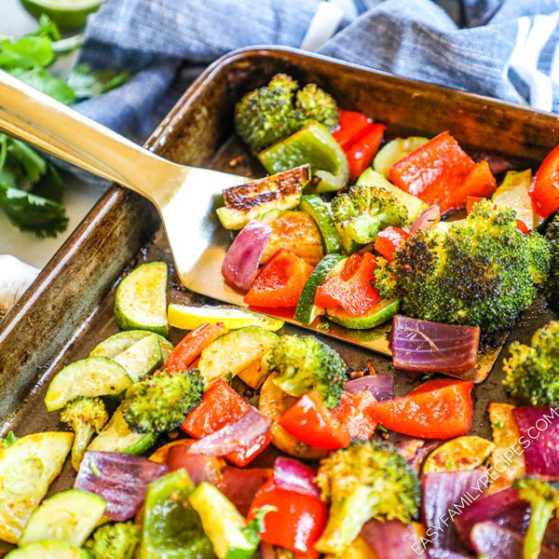 Mexican Roasted Vegetables being lifted from pan after baking